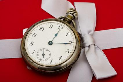 A pocket watch sitting on a red present background, time management